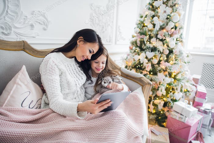 Beautiful young woman and her daughter with the tablet at Christmas time. Close-up.