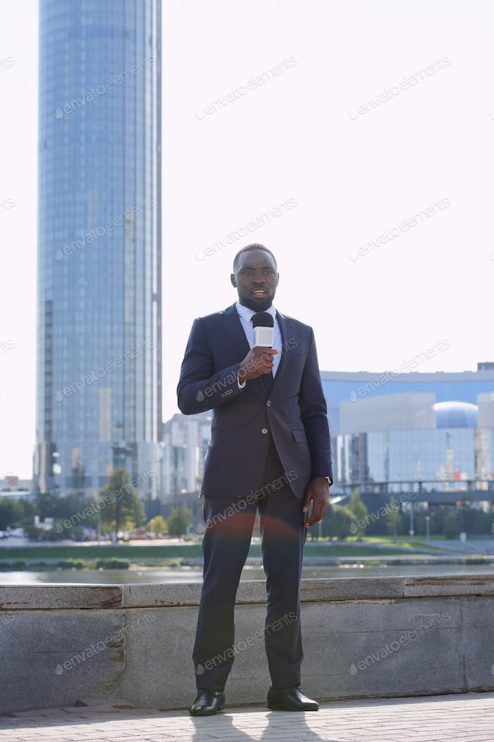 Young elegant journalist of African ethnicity talking to microphone outdoors