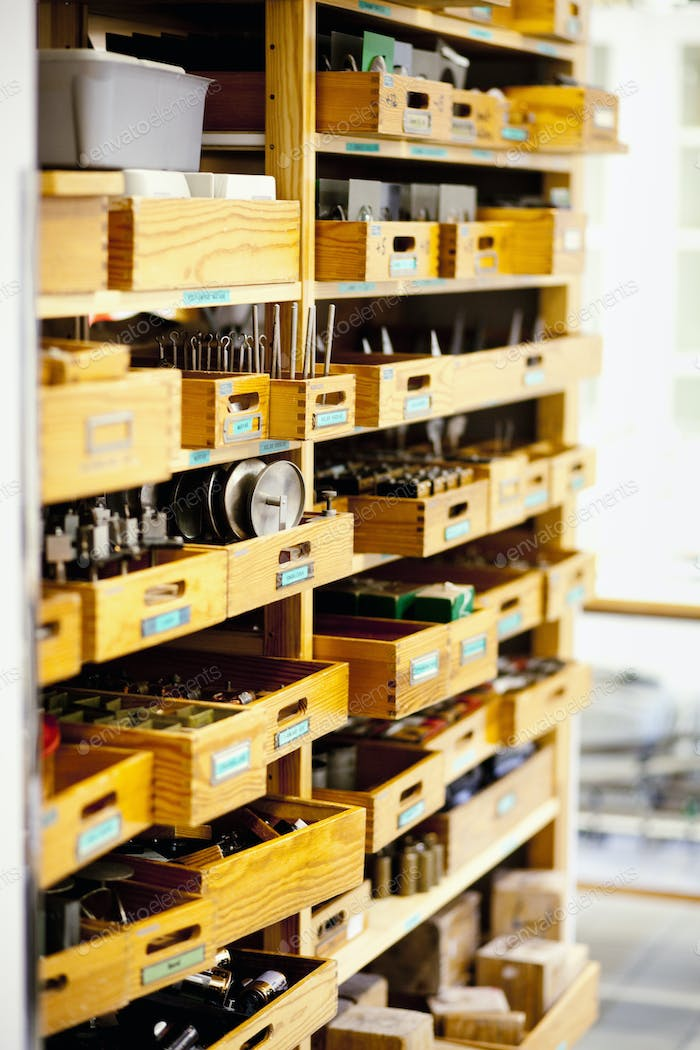 Spare parts in wooden drawers at industry