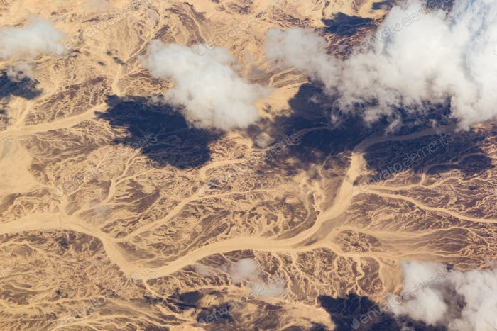 Clouds over a desert landscape. View from the airplane window