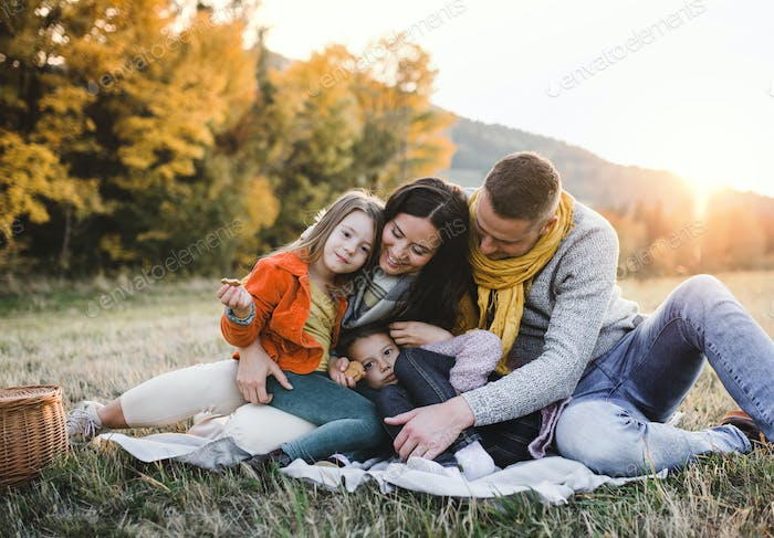 A portrait of young family with two small children in autumn nature at sunset