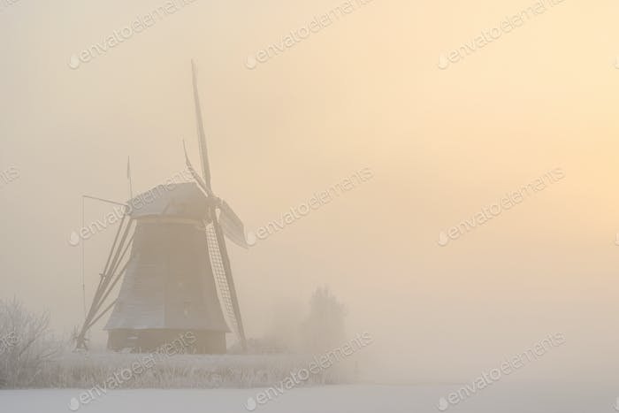 Sunrise over a windmill on a foggy winter morning