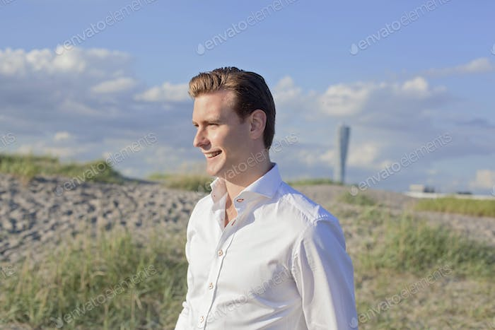 Smiling young man standing on field