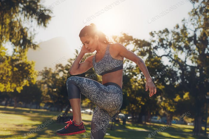 Young woman doing stretching workout at a park.