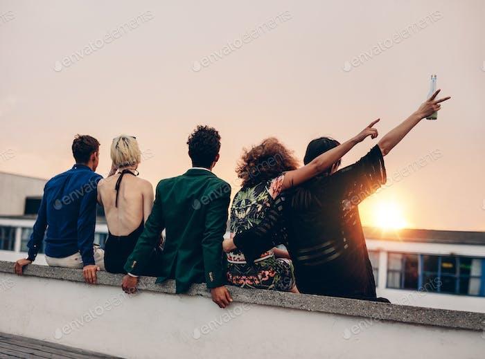 Freunde genießen Getränke auf dem Dach bei Sonnenuntergang