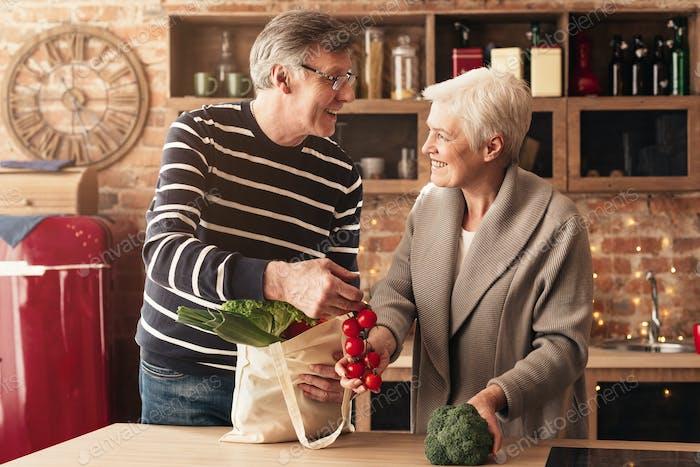 Senior couple unpacking shopping bags in kitchen