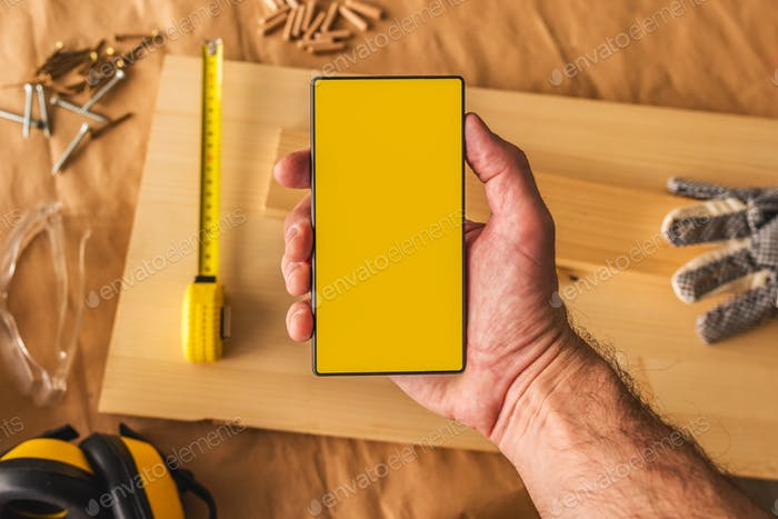 Carpenter holding modern smartphone with blank mock up screen