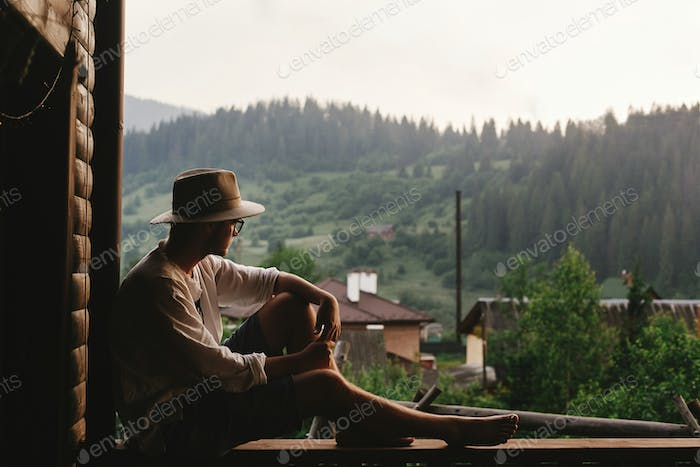 Hipster man sitting on porch of wooden house  looking at mountains in evening