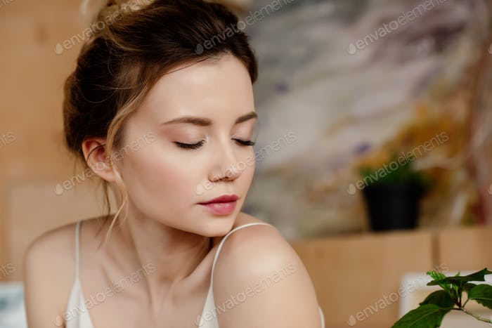 close-up portrait of beautiful tender girl with closed eyes in art studio