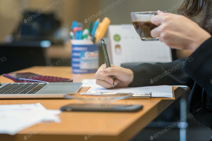Closeup businesswoman hand writing and drinking coffee when working
