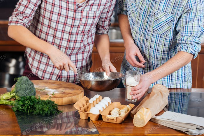 Hands of couple beating eggs and cooking together on kitchen