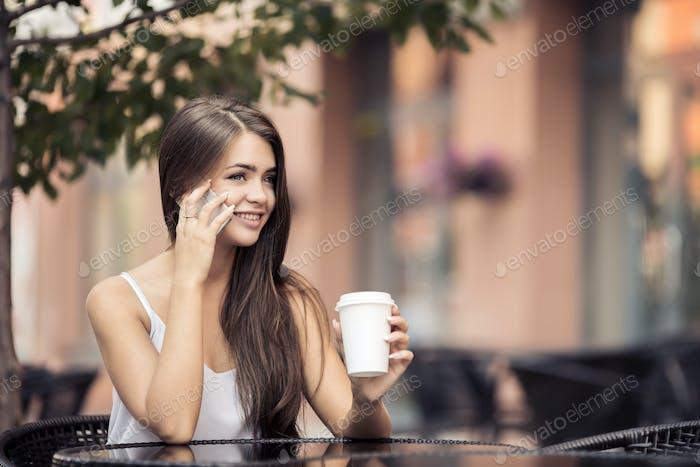 Young Beautiful Woman In Coffee Shop Talking On Phone.