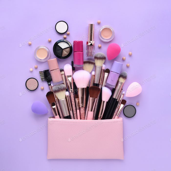 A pink cosmetics bag with professional makeup brushes and makeup products spilling out