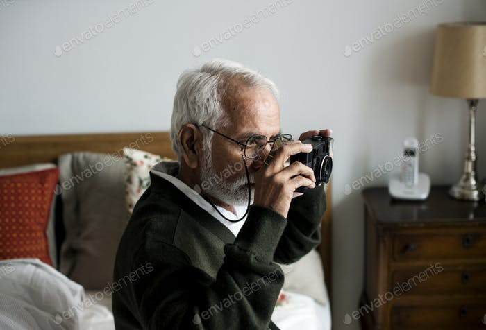An elderly Indian man at the retirement house taking a photo
