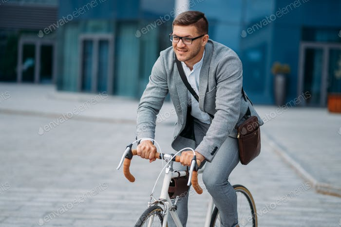 Businessman poses on bicycle at office building