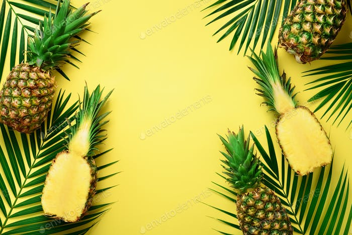 Pineapples and tropical palm leaves on punchy pastel yellow background. Summer concept. Creative