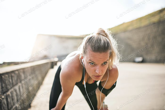 Young sporty woman runner with earphones resting outside by the sea.