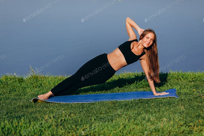 girl holds asana side lath while on yoga mat and looking at tha camera