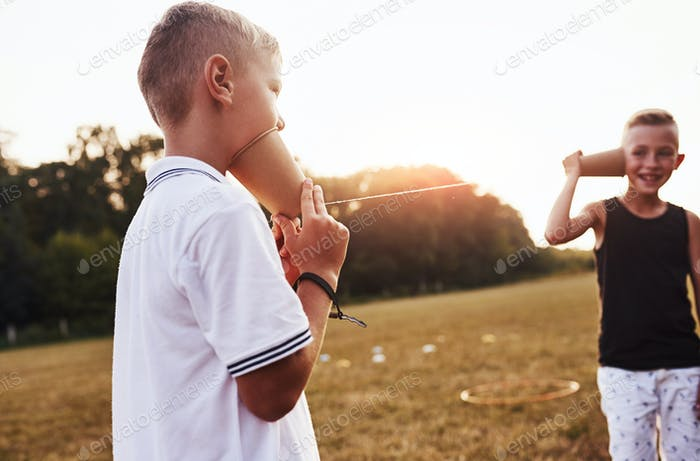 Two boys stands in the field and talking by using string can phone