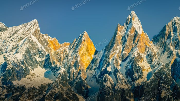 Landscape view of mountain range and peaks lit by golden sunlight, Himalayas