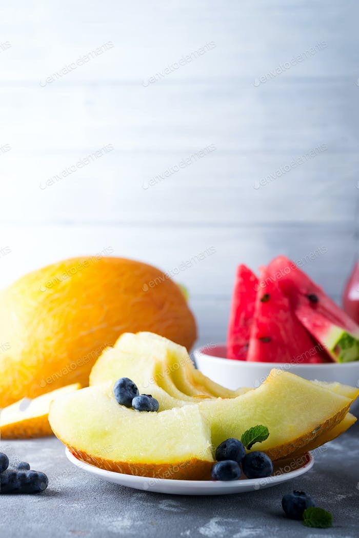 ripe sliced watermelon and melon isolated on gray