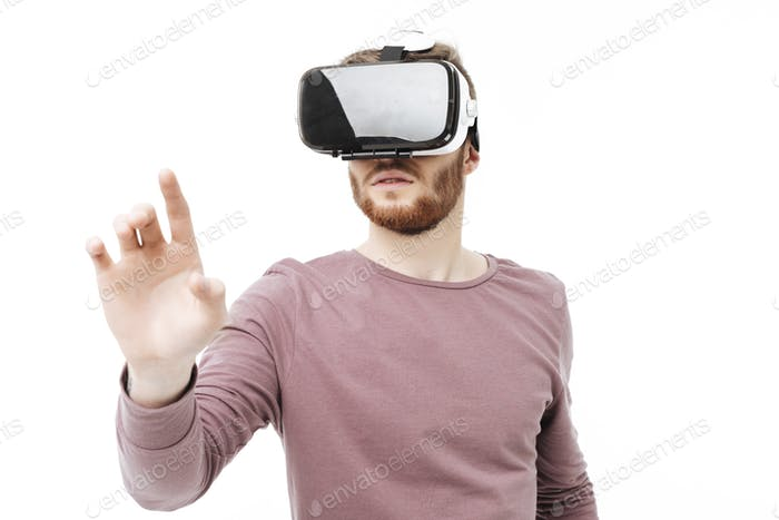 Portrait of young thoughtful man using virtual reality glasses over white background