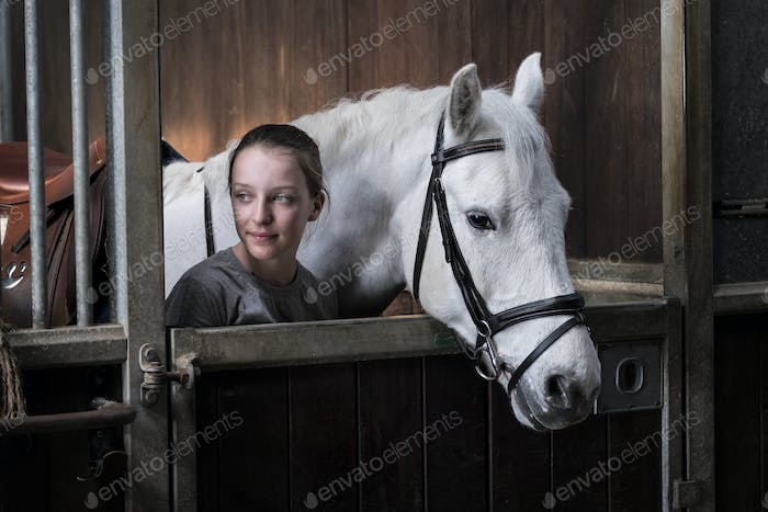 Teenage girl horserider with a grey horse outside astable, adjusting the girth and saddle.