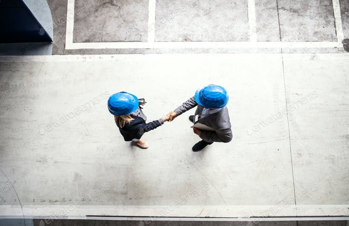 A top view of an industrial man and woman engineer in a factory, shaking hands.