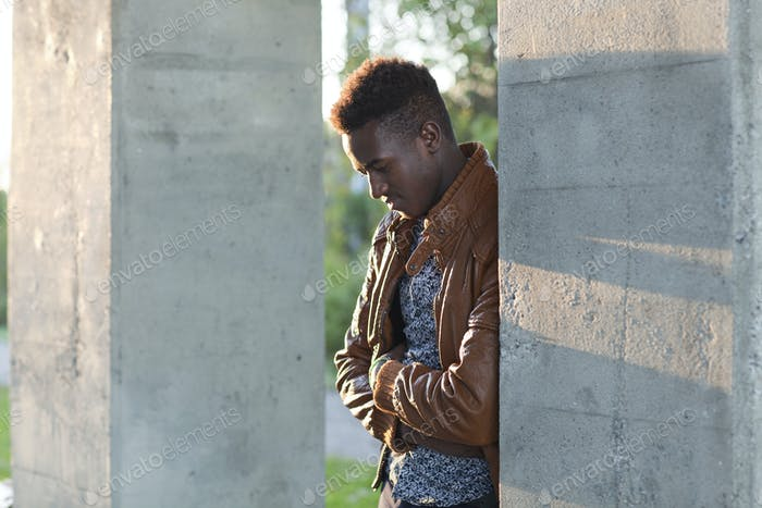 Young black man looking down leaning on a wall
