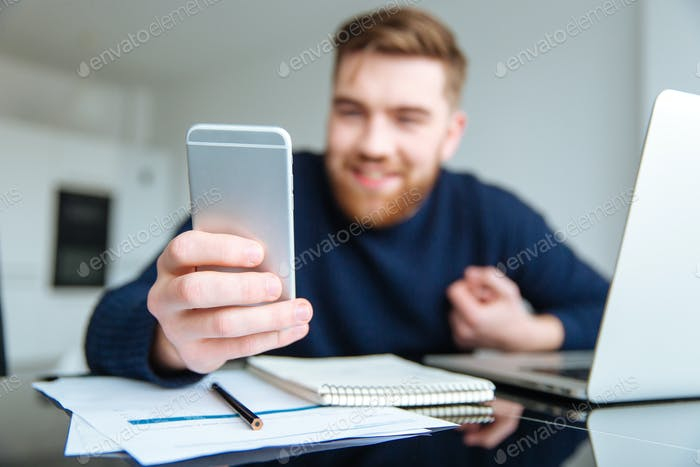 Man sitting at the table and using smartphone