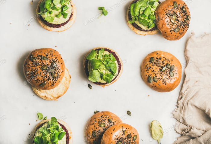 Healthy burgers with beetroot patties, avocado cream and green sprouts