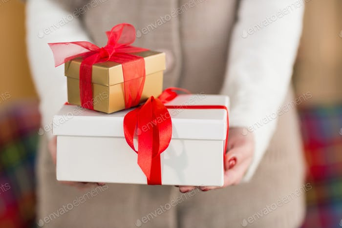 Woman with nail varnish holding gifts at home in the living room