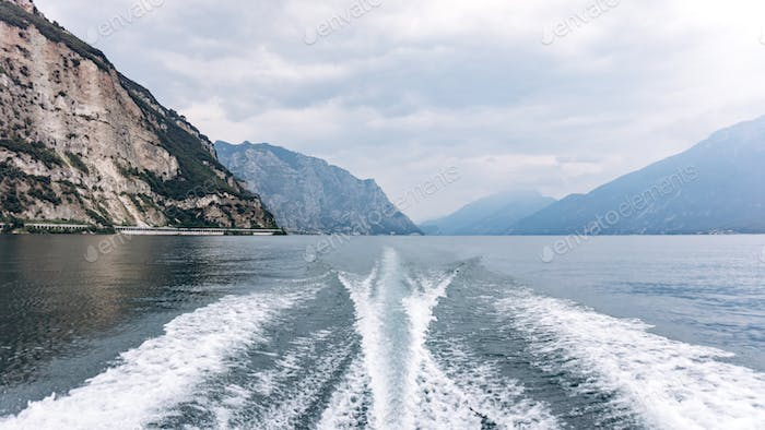 On the water traces from the boat, the landscape of mountains and forests.