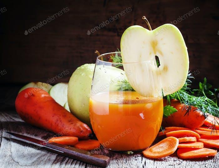 ApfelKarottensaft in einem großen Glas mit einer Scheibe grünen Apfel