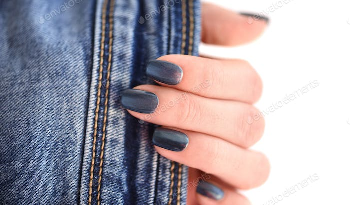 Female hand with dark blue manicured nails with jeans on white b