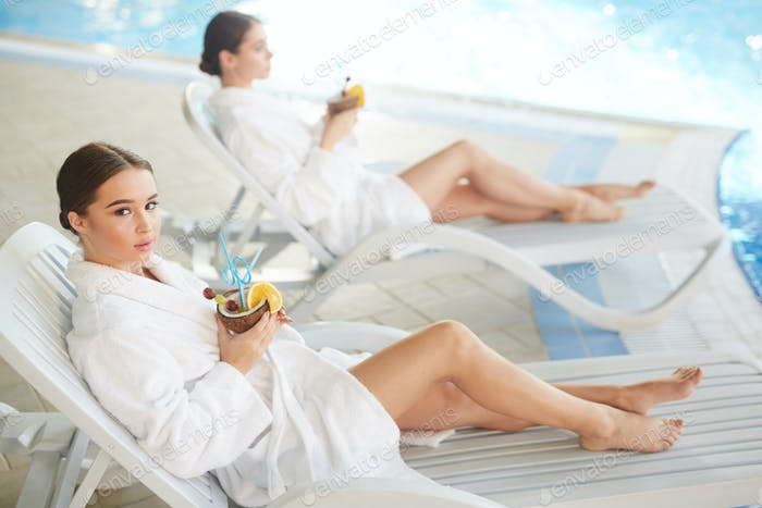 Young Women Relaxing by Swimming Pool
