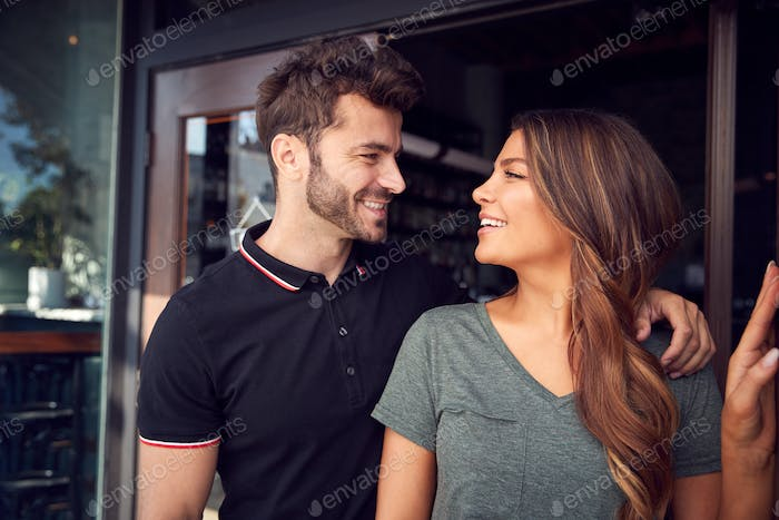 Couple Starting New Coffee Shop Or Restaurant Business Standing In Doorway