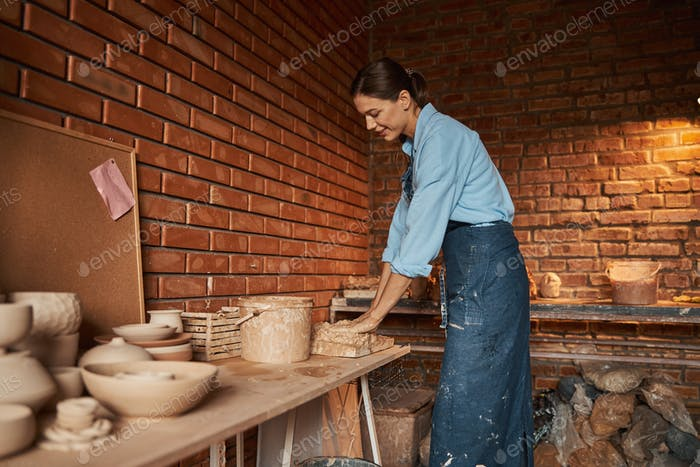 Young Caucasian craftswoman hanging out in art studio while squeezing earthenware materials in art