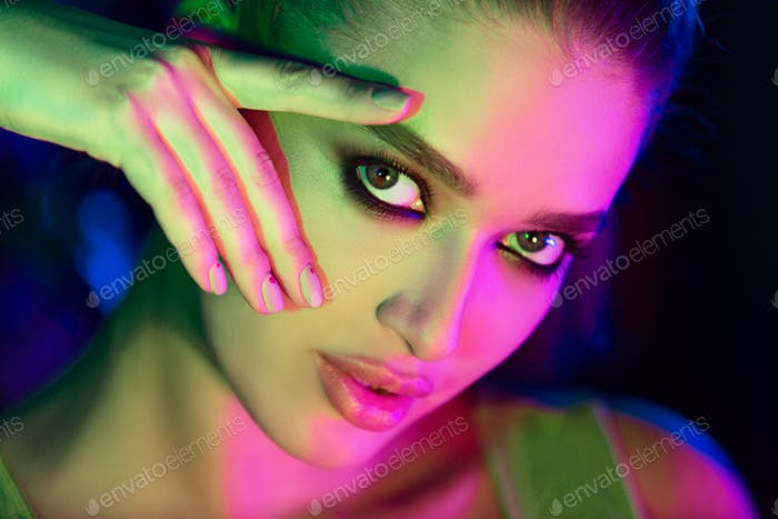 Girl with trendy make-up in colorful bright lights
