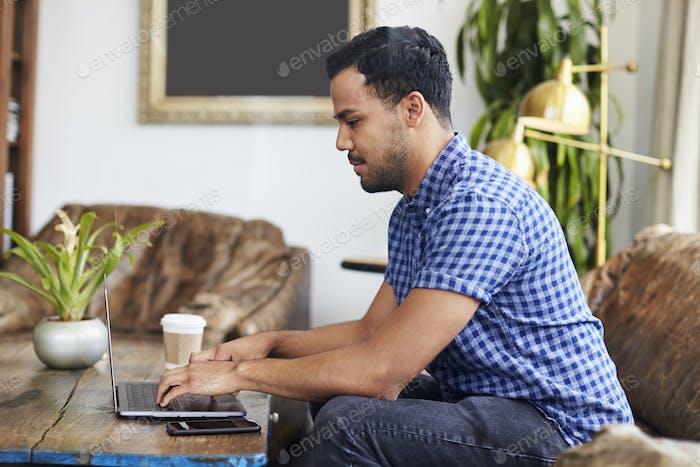 Junge spanische Mann sitzt in einem Café mit Laptop