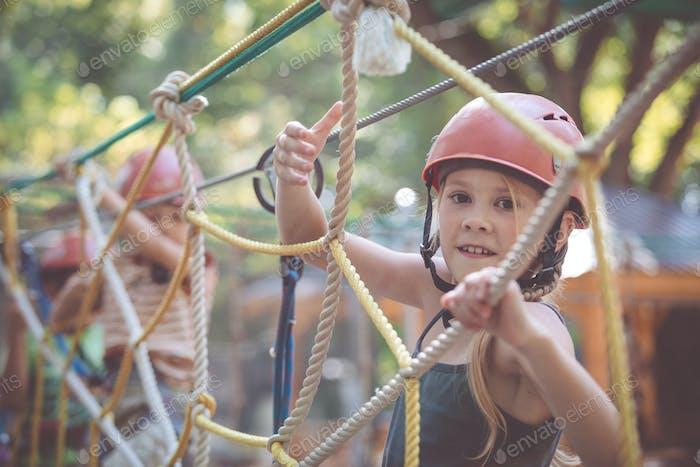 kleine Bruder und Schwester machen Klettern im Abenteuerpark.