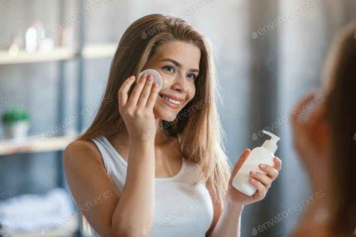 Lovely young woman using makeup remover or facial lotion in front of mirror at bathroom