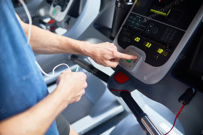 Closeup of Man Setting Machine in Gym