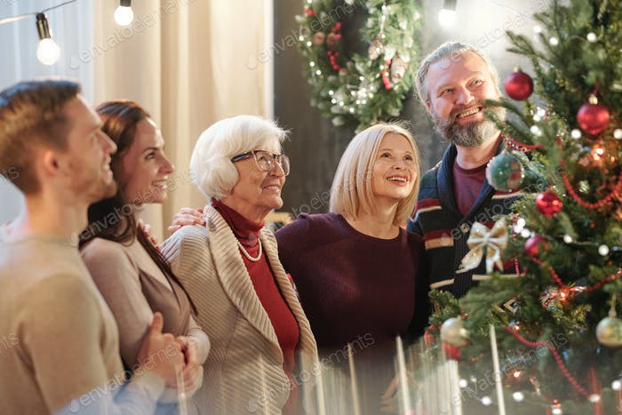 Happy family of five adults looking at decorated Christmas tree