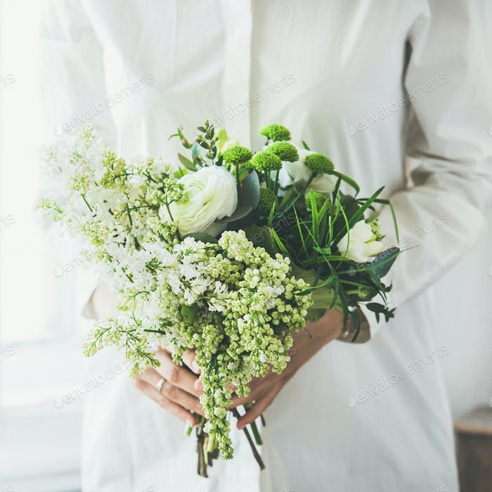 Young woman wearing white clothes holding flowers bouquet, square crop