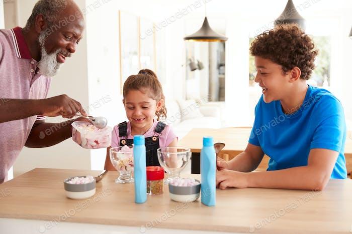 Großvater Serving Eis zu Enkelkinder in Küche