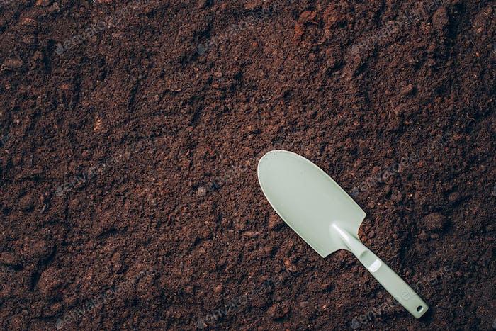 Kleine Schaufel mit Händel über Bodenhintergrund. Landwirtschaft, Bio-Gartenbau, Pflanzung oder Ökologie