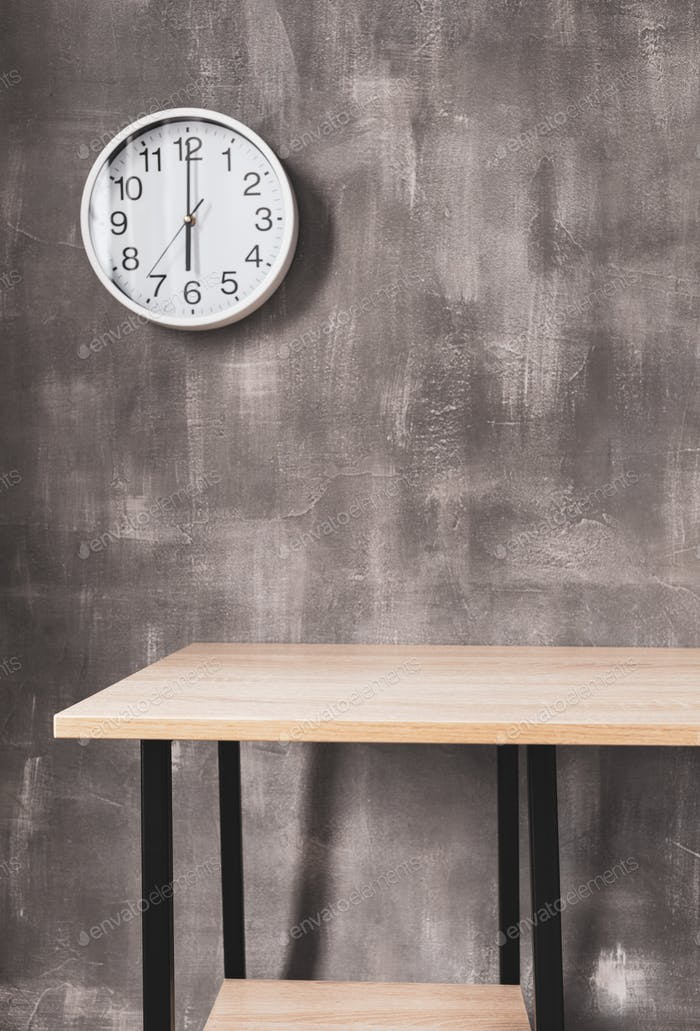 wooden table and wall clock near wall