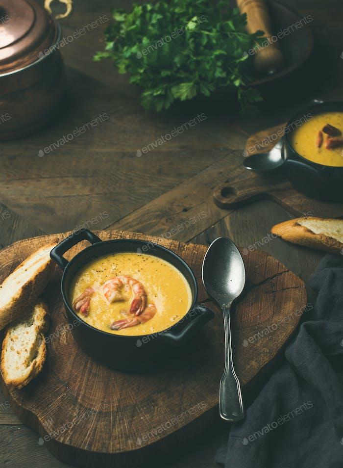 Corn creamy soup with shrimps served in individual pots