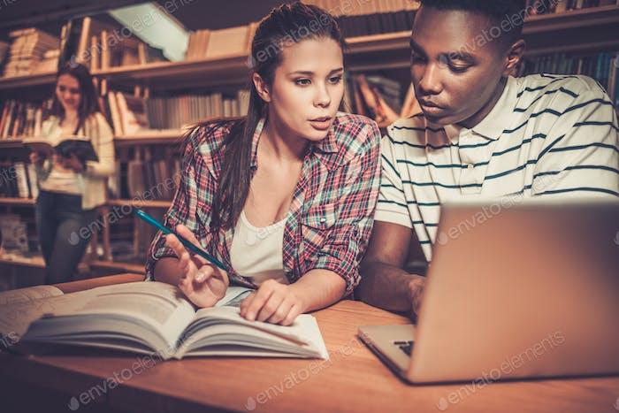 Multinationale Gruppe von fröhlichen Studenten, die in der Universitätsbibliothek studieren.